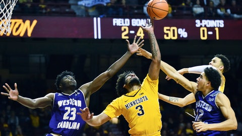 Minnesota forward Jordan Murphy (3) fights for a loose ball with Western Carolina forwards Mike Amius (23) and Marc Gosselin, right, during the second half an NCAA college basketball game, Sunday, Nov. 19, 2017, in Minneapolis. Minnesota won, 92-64. (AP Photo/John Autey)