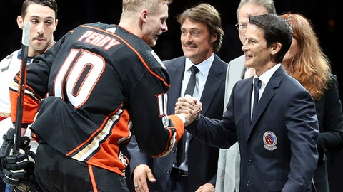 Anaheim Ducks right winger Corey Perry (10) shakes congratulates NHL Hall of Fame inductees and former Anaheim Ducks Paul Kariya, right, and Teemu Selanne, center, after a ceremonial puck drop as the pair are honored before a hockey game between the Ducks and the Florida Panthers in Anaheim, Calif., Sunday, Nov. 11, 2017. (AP Photo/Reed Saxon)