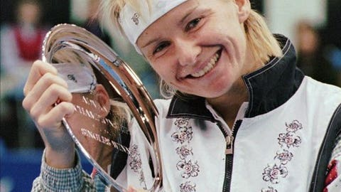 FILE - In this Nov. 17, 1996 file photo, Jana Novotna, of the Czech Republic, is all smiles after taking home a $79,000 check from the Advanta Tennis Championship in Villanova, Pa. The WTA says the 1998 Wimbledon champion Jana Novotna of the Czech Republic has died. In a Monday, Nov. 20, 2017 statement, the WTA say Novotna died after battling a cancer on Sunday, Nov. 19. She was 49.(AP Photo/Jim Graham, File)