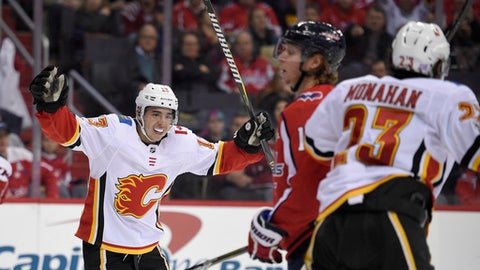Calgary Flames left wing Johnny Gaudreau (13) celebrates a goal by center Sean Monahan (23) during the second period of an NHL hockey game Washington Capitals center Nicklas Backstrom, center, of Sweden, skates by, Monday, Nov. 20, 2017, in Washington. (AP Photo/Nick Wass)