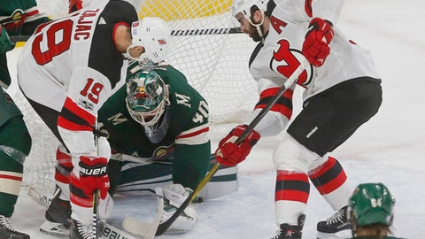 Minnesota Wild goalie Devan Dubnyk, center, defends the goal as New Jersey Devils' Travis Zajac, left, and Kyle Palmieri try to free the puck in the second period of an NHL hockey game Monday, Nov. 20, 2017, in St. Paul, Minn. (AP Photo/Jim Mone)