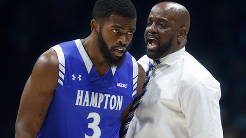 Hampton's head coach Edward Joyner Jr., right, speaks with Trey Carver (3) in the first half of an NCAA college basketball game against Xavier, Monday, Nov. 20, 2017, in Cincinnati. (AP Photo/John Minchillo)