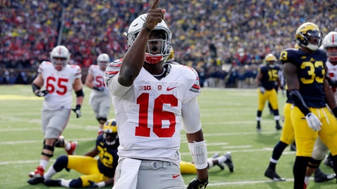 FILE - In this Nov. 28, 2015, file photo, Ohio State quarterback J.T. Barrett (16) points to the crowd after a touchdown during the second half of an NCAA college football game against Michigan, in Ann Arbor, Mich. Barrett has shattered nearly every Ohio State passing and scoring record but isn't considered a top NFL prospect. He helped win a national championship but has heard hysterical fans demand that he be benched. For all of his ups and downs through five years at Ohio State, Barrett  _ who plays his last regular-season game Saturday against Michigan _ is undeniably a winner. (AP Photo/Carlos Osorio, File)
