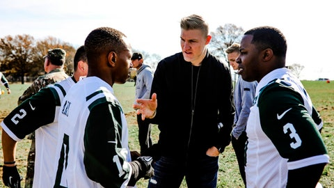 In this photo provided by the New York Jets, New York Jets quarterback Josh McCown, center, huddles up with his squad of military members at Fort Hamilton Army Base during a game of flag football in Brooklyn borough of New York, Tuesday, Nov. 21, 2017. McCown and Jets teammate Demario Davis served as coaches for the service members. McCown's team beat Davis' squad 18-14. (New York Jets.com/New York Jets via AP)