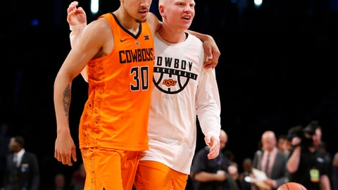 Oklahoma State guard Jeffrey Carroll, left, and Oklahoma State forward Trey Reeves, right, celebrate after during OSU defeated Pittsburgh 73-67 in an NCAA college basketball game in the Legends Classic tournament, Tuesday, Nov. 21, 2017, in New York. (AP Photo/Kathy Willens)
