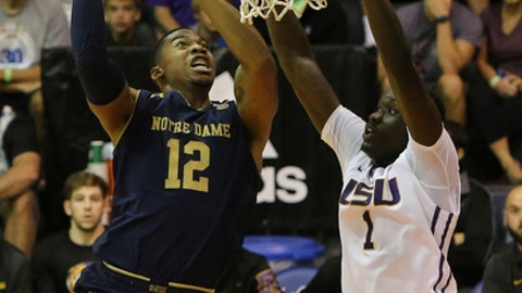 Notre Dame forward Elijah Burns (12) goes to the net as LSU forward Duop Reath (1) guards him during the first half of an NCAA college basketball game, Tuesday, Nov. 21, 2017, in Lahaina, Hawaii. (AP Photo/Marco Garcia)