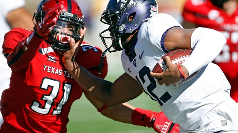 FILE - In this Saturday, Nov. 18, 2017, file photo, TCU's Shawn Robinson (12) tries to run around Texas Tech's Justus Parker (31) during the second half of an NCAA college football game in Lubbock, Texas. quarterback to step up as the regular season winds down.  For the Horned Frogs, Shawn Robinson became the first true freshman quarterback to start for coach Gary Patterson in his 17 seasons as the head coach in last week's 27-3 win over Texas Tech. (AP Photo/Brad Tollefson, File)