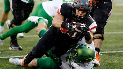 FILE - In this Nov. 26, 2016, file photo, Oregon State running back Ryan Nall, top, dives over Oregon's Danny Mattingly for a touchdown in the second half an NCAA college football game in Corvallis, Ore. Last year at this time, Oregon's coach was on the verge of being dismissed and Oregon State was about to finally win a Civil War after eight seasons of futility. . (AP Photo/Timothy J. Gonzalez, File)
