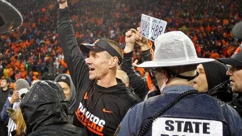 FILE - In this Nov. 26, 2016, file photo, Oregon State head coach Gary Andersen, center, celebrates after their 34-24 win over Oregon in an NCAA college football game in Corvallis, Ore. Last year at this time, Oregon's coach was on the verge of being dismissed and Oregon State was about to finally win a Civil War after eight seasons of futility.  (AP Photo/Timothy J. Gonzalez, File)