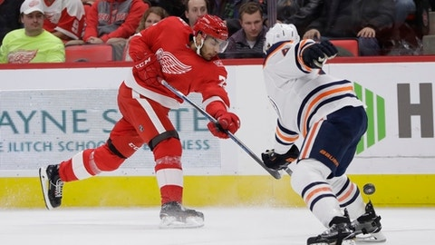 Detroit Red Wings left wing Andreas Athanasiou shoots past Edmonton Oilers defenseman Kris Russell during the second period of an NHL hockey game, Wednesday, Nov. 22, 2017, in Detroit. (AP Photo/Carlos Osorio)