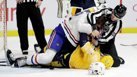 Linesman David Brisebois (96) tries to stop a fight between Montreal Canadiens defenseman Karl Alzner (22) and Nashville Predators center Kyle Turris (8) during the third period of an NHL hockey game Wednesday, Nov. 22, 2017, in Nashville, Tenn. The Predators won 3-2 in a shootout. (AP Photo/Mark Humphrey)