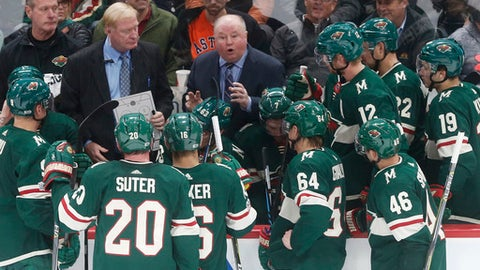 "FILE - In this Oct. 31, 2017, file photo, Minnesota Wild coach Bruce Boudreau, center, talks to players during a timeout in the teams NHL hockey game against the Winnipeg Jets in St. Paul, Minn. Boudreau, whose Wild are 13th in the West but just two points out of a playoff spot, doesn't think much about the Thanksgiving rule. ""If you look at it as this is a truism and you're not in at that time, you have a tendency to (think), 'Aw man, we're not going make it,' and I don't want anybody on our team thinking along those lines,"" Boudreau said. ""But it's going to be close. Everybody's 8-9, 9-8, 10-9, 9-10."" (AP Photo/Jim Mone)"