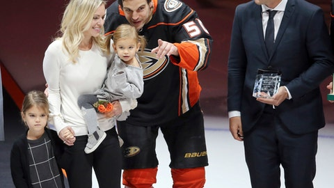 Anaheim Ducks center Antoine Vermette is joined by, from left, his daughter Leonna, wife Karen holding daughter Emilia, and former NHL player Shane Doan as he is honored for his 1,000th NHL game before an NHL hockey game against the Vegas Golden Knights in Anaheim, Calif., Wednesday, Nov. 22, 2017. (AP Photo/Reed Saxon)