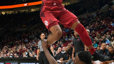 Oklahoma guard Christian James, top, is fouled by Arkansas forward Adrio Bailey, bottom, during the first half of an NCAA college basketball game at the Phil Knight Invitational tournament in Portland, Ore., Thursday, Nov. 23, 2017. (AP Photo/Troy Wayrynen)