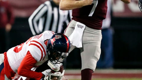Mississippi State quarterback Nick Fitzgerald (7) is tackled by Mississippi's Zedrick Woods during the first half of an NCAA college football game in Starkville, Miss., Thursday, Nov. 23, 2017. (AP Photo/Rogelio V. Solis)
