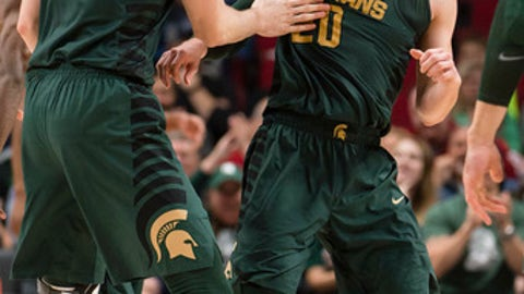 Michigan State guard Matt McQuaid, center, celebrates with forward Ben Carter, left, after making a three point basket during the second half in an NCAA college basketball game at the Phil Knight Invitational Tournament in Portland, Ore., Thursday Nov. 23, 2017. (AP Photo/Troy Wayrynen)