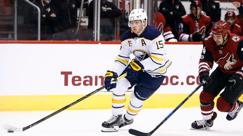 FILE- In this Nov. 2, 2017, file photo, Buffalo Sabres center Jack Eichel (15) skates with the puck in front of Arizona Coyotes center Zac Rinaldo (34) during the first period of an NHL hockey game in Glendale, Ariz. Eichel signed an eight-year, $10 million deal, which is tied for the 10th richest contract in league history. (AP Photo/Ross D. Franklin, File)