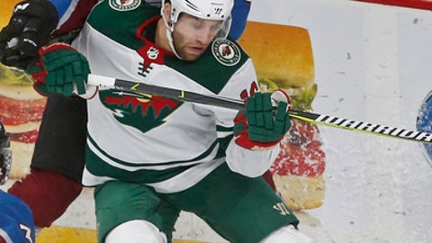 Colorado Avalanche's Tyson Barrie, left, closes in on Minnesota Wild's Jason Zucker as they pursue the puck along the boards in the second period of an NHL hockey game Friday, Nov. 24, 2017, in St. Paul, Minn. (AP Photo/Jim Mone)