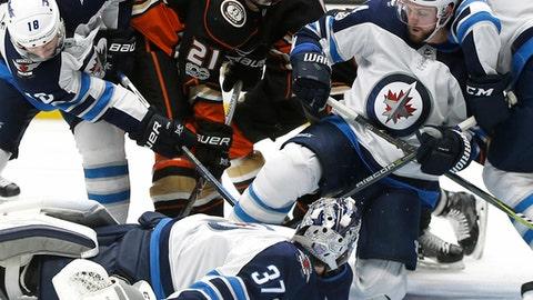 Winnipeg Jets goalie Connor Hellebuyck (37) lies on the puck as center Bryan Little (18), defenseman Josh Morrissey (44) and defenseman Jacob Trouba (8) defend against Anaheim Ducks center Chris Wagner (21) during the second period of an NHL hockey game in Anaheim, Calif., Friday, Nov. 24, 2017. (AP Photo/Alex Gallardo)