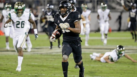 Central Florida's Mike Hughes returns a kickoff for a 95-yard game winning touchdown past South Florida defensive back Craig Watts (26) during the second half of an NCAA college football game, Friday, Nov. 24, 2017, in Orlando, Fla. Central Florida won 49-42 (AP Photo/John Raoux)