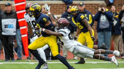Michigan wide receiver Donovan Peoples-Jones (9) returns a punt and attempts to break a tackle from Ohio State wide receiver Terry McLaurin (83), in the first quarter of an NCAA college football game in Ann Arbor, Mich., Saturday, Nov. 25, 2017. (AP Photo/Tony Ding)