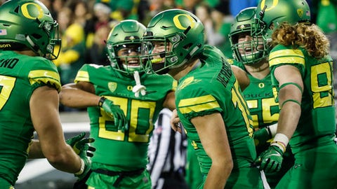 Oregon quarterback Justin Herbert (10), celebrates his second quarter touchdown with teammates against Oregon State in an NCAA college football game Saturday, Nov. 25, 2017 in Eugene, Ore. (AP Photo/Thomas Boyd)