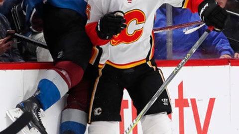 Calgary Flames defenseman Michael Stone, right, checks Colorado Avalanche left wing Gabriel Landeskog, of Sweden, in the second period of an NHL hockey game Saturday, Nov. 25, 2017, in Denver. (AP Photo/David Zalubowski)