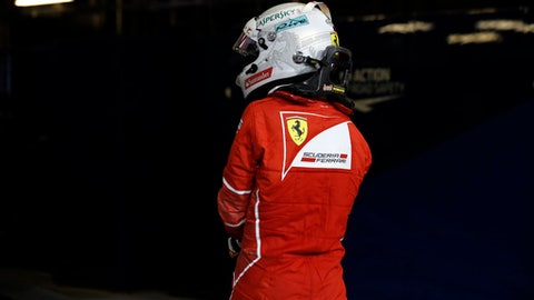 Ferrari driver Sebastian Vettel of Germany walks to the podium after finishing third in the Emirates Formula One Grand Prix at the Yas Marina racetrack in Abu Dhabi, United Arab Emirates, Sunday, Nov. 26, 2017. (AP Photo/Hassan Ammar)