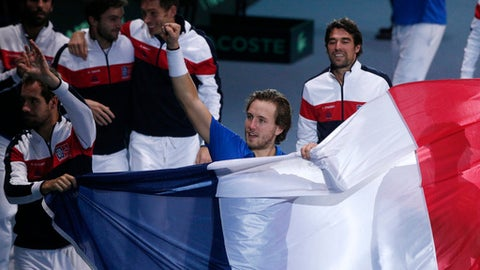 France's Lucas Pouille, center, carries the French flag with teammates after he defeated Belgium's Steve Darcis in their Davis Cup final single match at the Pierre Mauroy stadium in Lille, northern France, Sunday, Nov. 26, 2017. France won the Davis Cup for the first time in 16 years after Lucas Pouille beat Belgium's Steve Darcis to clinch the decisive point of the final. (AP Photo/Michel Spingler)
