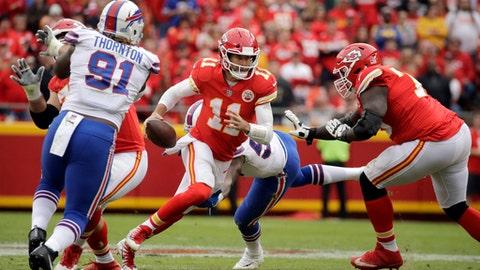 Kansas City Chiefs quarterback Alex Smith (11) runs between offensive lineman Zach Fulton (73) and Buffalo Bills defensive tackle Cedric Thornton (91) during the first half of an NFL football game in Kansas City, Mo., Sunday, Nov. 26, 2017. (AP Photo/Charlie Riedel)