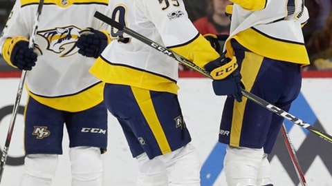 Nashville Predators' Roman Josi (59), of Switzerland, and Kevin Fiala, left, also of Switzerland, congratulate Juuse Saros (74) following Saros' goal against the Carolina Hurricanes during the second period of an NHL hockey game in Raleigh, N.C., Sunday, Nov. 26, 2017. (AP Photo/Gerry Broome)