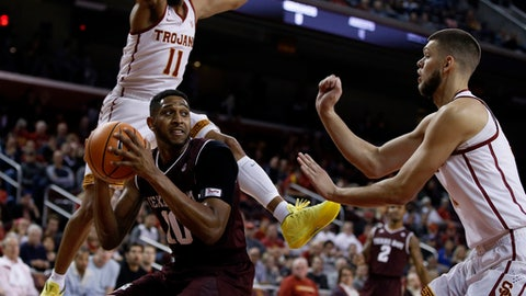 Southern California guard Jordan McLaughlin (11) leaps to defend against Texas A&M center Tonny Trocha-Morelos (10) with forward Nick Rakocevic, right, during the first half of an NCAA college basketball game in Los Angeles, Sunday, Nov. 26, 2017. (AP Photo/Alex Gallardo)