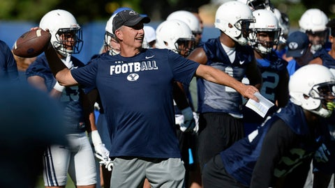 """FILE - In this July 27, 2017, file photo, BYU football offensive coordinator and quarterbacks coach Ty Detmer works with the team during NCAA college football practice in Provo, Utah. Ty Detmer is no longer the offensive coordinator at BYU. The school announced Monday, Nov. 27, 2017, that the Heisman Trophy winner """"has been relieved of his role as the team's offensive coordinator.""""(Francisco Kjolseth/The Salt Lake Tribune via AP, File)"""