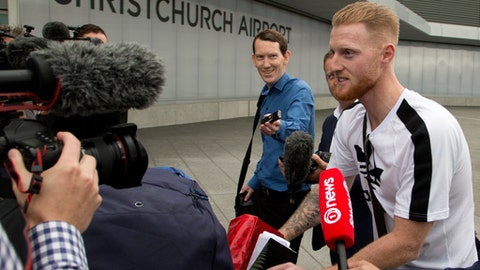 New Zealand-born England cricket star Ben Stokes, right, is surrounded by media as he arrives in Christchurch, New Zealand, Wednesday, Nov. 29, 2017. Stokes is in New Zealand to visit family and possibly play for Canterbury province during his stay. (AP Photo/Mark Baker)