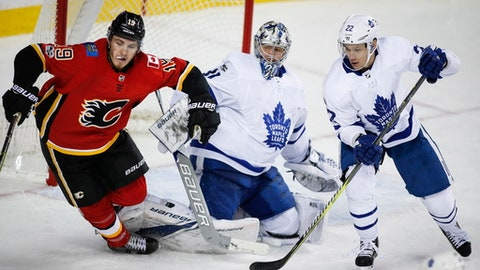 Toronto Maple Leafs goalie Frederik Andersen, center, from Denmark, and teammate Nikita Zaitsev, right, from Russia, look on as Calgary Flames' Matthew Tkachuk trips over Andersen's pads during the third period of an NHL hockey game in Calgary, Alberta, Tuesday, Nov. 28, 2017. Toronto won, 4-1. (Jeff McIntosh/The Canadian Press via AP)