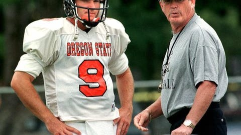 In this Wednesday, Aug. 18, 1999 file photo, Oregon State head football coach Dennis Erickson talks strategy with quarterback Jonathan Smith during practice in Corvallis, Ore. A person with direct knowledge of the decision says Oregon State has hired Washington co-offensive coordinator Jonathan Smith to be its new head coach. The person spoke to The Associated Press on Wednesday, Nov. 29, 2017 on condition of anonymity because an official announcement was being finalized.  (AP Photo/Don Ryan, File)