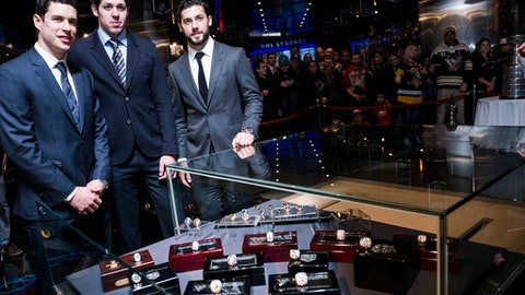 Pittsburgh Penguins' Sidney Crosby, Evgeni Malkin and Chris Letang, from left, gather for a photo next to a display case holding the 2017 NHL hockey Stanley Cup champions' ring that was donated to the Hockey Hall of Fame by the Penguins, in Toronto on Wednesday, Nov. 29, 2017. (Christopher Katsarov/The Canadian Press via AP)