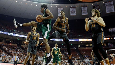 Florida A&M guard Brendon Myles pulls down a rebound in front of Texas guard Jase Febres (13) during the first half of an NCAA college basketball game, Wednesday, Nov. 29, 2017, in Austin, Texas. (AP Photo/Eric Gay)