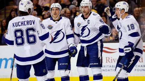 Tampa Bay Lightning's Steven Stamkos is congratulated by Ondrej Palat (18), Nikita Kucherov (86) and Yanni Gourde after scori8ng against the Boston Bruins during the third period of an NHL hockey game in Boston Wednesday, Nov. 29, 2017. (AP Photo/Winslow Townson)