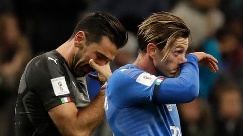 FILE- In this Monday, Nov. 13, 2017 file photo, Italy's goalkeeper Gianluigi Buffon, left, and Federico Bernardeschi react to their team's elimination in the World Cup qualifying play-off second leg soccer match between Italy and Sweden, at the Milan San Siro stadium, Italy. FIFA's top salesman insists the 2018 World Cup will make its income target even after taking a financial hit from Italy and the United States failing to qualify. (AP Photo/Luca Bruno, File)