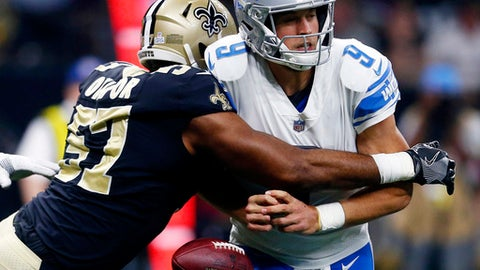 FILE - In this Oct. 15, 2017, file photo, Detroit Lions quarterback Matthew Stafford (9) fumbles as he is hit by New Orleans Saints defensive end Alex Okafor (57), causing a touchdown on the fumble recovery in the end zone, in the first half of an NFL football game in New Orleans. The Baltimore Ravens (6-5) lead the NFL with 18 interceptions and 26 takeaways. They have three shutouts, and last Monday they forced Houston quarterback Tom Savage into three turnovers in a 23-16 victory. Detroit quarterback Matthew Stafford has thrown eight interceptions and lost six fumbles this season. If the Lions (6-5) are to stay in the playoff hunt, Stafford must protect the football. (AP Photo/Butch Dill, File)