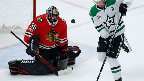Chicago Blackhawks' Corey Crawford, left, makes a save in front of Dallas Stars' Jason Spezza during the second period of an NHL hockey game Thursday, Nov. 30, 2017, in Chicago. (AP Photo/Jim Young)