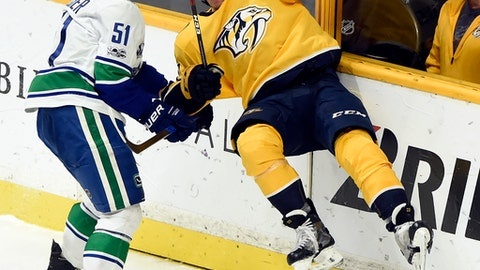 Vancouver Canucks defenseman Troy Stecher (51) checks Nashville Predators left wing Kevin Fiala (22), of Switzerland, into the boards during the third period of an NHL hockey game Thursday, Nov. 30, 2017, in Nashville, Tenn. The Canucks won 5-3. (AP Photo/Mark Zaleski)