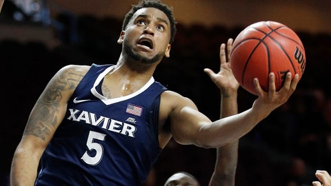 Xavier's Trevon Bluiett shoots around George Washington's Yuta Watanabe, left, during the first half of an NCAA college basketball game Thursday, Nov. 23, 2017, in Las Vegas. (AP Photo/John Locher)