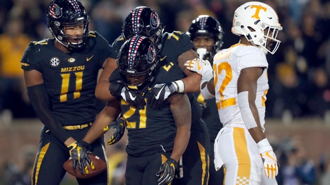 Missouri's Ish Witter (21) is congratulated by teammates Kendall Blanton (11) and Kevin Pendleton (71) as Tennessee defensive back Micah Abernathy (22) walks past after Witter scored on a touchdown run during the first half of an NCAA college football game Saturday, Nov. 11, 2017, in Columbia, Mo. (AP Photo/Jeff Roberson)