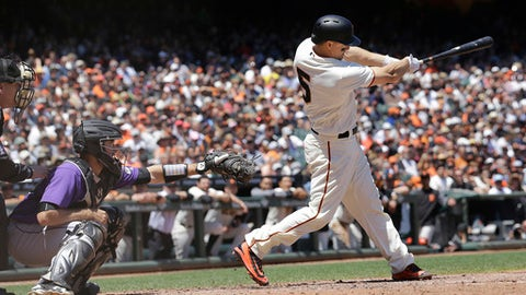 San Francisco Giants' Nick Hundley, right, hits a two-run home run in front of Colorado Rockies catcher Tom Murphy during the fourth inning of a baseball game in San Francisco, Wednesday, June 28, 2017. (AP Photo/Jeff Chiu)