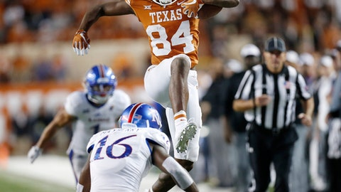 Texas wide receiver Lil'Jordan Humphrey (84) leaps over Kansas corner back Kyle Mayberry (16) in the second half of an NCAA college football game  Saturday, Nov. 11, 2017, in Austin, Texas. (Stephen Spillman /Austin American-Statesman via AP)