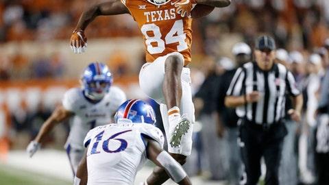 Texas wide receiver Lil'Jordan Humphrey (84) leaps over Kansas corner back Kyle Mayberry (16) in the second half of an NCAA college football game  Saturday, Nov. 11, 2017, in Austin, Texas. (Stephen Spillman /Austin American-Statesman via AP)
