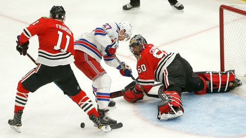 Chicago Blackhawks goalie Corey Crawford (50) makes a save on a shot by New York Rangers' Ryan McDonagh (27) as Cody Franson also defends during the first period of an NHL hockey game, Wednesday, Nov. 15, 2017, in Chicago. (AP Photo/Charles Rex Arbogast)