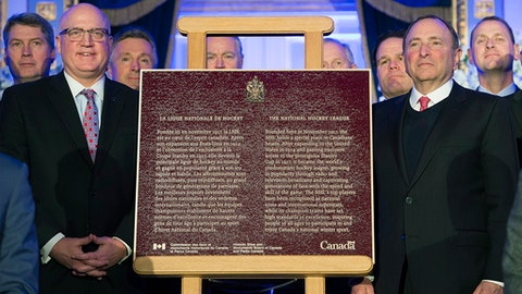 NHL commissioner Gary Bettman, right, and NHL deputy commissioner Bill Daly, left, with league general managers pose next to a plaque to commemorate 100 years of the league during a ceremony in Montreal, Friday, Nov. 17, 2017.  (Graham Hughes/The Canadian Press via AP)